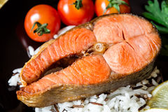 Fried salmon steak with vegetables and rice on plate Stock Photo