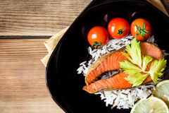 Fried salmon steak with vegetables and rice on plate Royalty Free Stock Photos