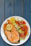 Fried salmon with vegetable salad and lemon on plate Stock Photos