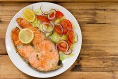 Fried salmon with vegetable salad and lemon on plate Stock Image