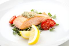 Fried Salmon With Wasabi Caviar. Close up of delicious pan fried salmon with unique wasabi caviar, tomatoes, and microgreens salad. Elite food Stock Photography
