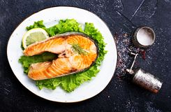 Fried salmon. On white plate and on a table royalty free stock image