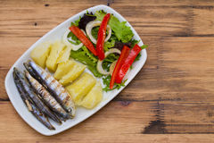 Fried sardines with boiled potato and salad on white plate Royalty Free Stock Images