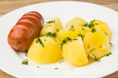 Fried sausage with boiled potatoes. A dish of boiled potatoes and fried sausages on a white plate Royalty Free Stock Photos