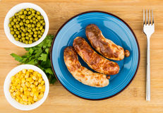 Fried sausage, green peas and sweet corn in and fork, top view Stock Photography