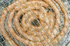 Fried sausage on the grill. Fried sausage lined with a spiral on a barbecue grill, like a background stock images
