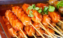 Fried sausage a grill on a stick in sauce Royalty Free Stock Image