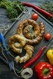 Fried sausage with herbs and spices, wooden background. Ring of baked homemade sausage. Served on a wooden board with a fork, stock image