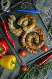 Fried sausage with herbs and spices, wooden background. Ring of baked homemade sausage. Served on a wooden board with a fork, royalty free stock photo