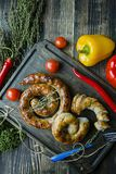 Fried sausage with herbs and spices, wooden background. Ring of baked homemade sausage. Served on a wooden board with a fork, stock photo
