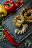 Fried sausage with herbs and spices, wooden background. Ring of baked homemade sausage. Served on a wooden board with greens and royalty free stock photos