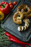 Fried sausage with herbs and spices, wooden background. Ring of baked homemade sausage. Served on a wooden board with greens and stock image