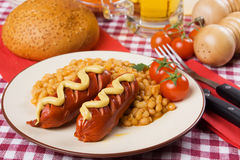 Fried sausage with mustard and cooked beans Royalty Free Stock Photography