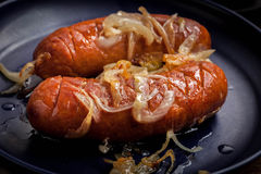 Fried sausage with onions. Stock Images