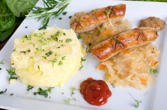 Fried sausage with pickled cabbage Royalty Free Stock Photos