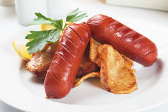 Fried sausage with potato chips Stock Photos