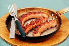 Fried sausage in a skillet. Stock Photos