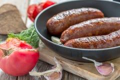 Fried sausage, tomato and garlic closeup. Royalty Free Stock Photos