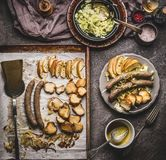 Fried sausages on baking tray served on plate with white coleslaw salad and mustard dip on rustic kitchen table, top view. German. Food concept Stock Image