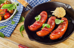 Fried sausages with fresh salad. On  a wooden table. Top view Stock Images