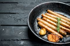 Fried sausages in a frying pan royalty free stock photo