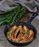 Fried sausages on a frying pan Stock Photos