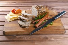 Fried sausages on green salad, bread, cherry tomatoes and cheese on wooden board. Close up Royalty Free Stock Photo