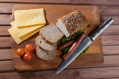 Fried sausages on green salad, bread, cherry tomatoes and cheese on wooden board, top view. Fried sausages on green salad, bread, cherry tomatoes and cheese on Royalty Free Stock Image