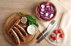 Fried sausages on the grill with cream sauce and a salad of radi. Sh with red cabbage on wooden background - top view Stock Photos