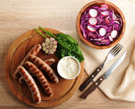 Fried sausages on the grill with cream sauce and a salad of radi. Sh with red cabbage on wooden background - top view Royalty Free Stock Photos