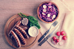 Fried sausages on the grill with cream sauce and a salad of radi. Sh with red cabbage on wooden background - top view in vintage aged style Stock Photo