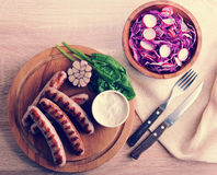 Fried sausages on the grill with cream sauce and a salad of radi. Sh with red cabbage on wooden background - top view in vintage aged style Royalty Free Stock Photo