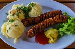 Fried sausages with mashed potatoes on a plate along with mustard, ketchup and greens royalty free stock photo