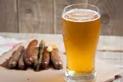 Fried sausages and mug of cold beer on a wooden table. Top view royalty free stock photography