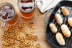 Fried sausages, on the pan with beer and pretzel Stock Photo