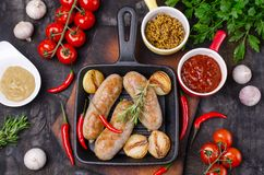 Fried sausages in a pan. On a dark background with raw vegetables. Selective focus royalty free stock photos