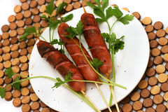 Fried sausages with parsley on dish. Fried sausages on white dish with parsley Stock Image