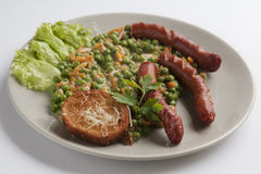 Fried sausages with peas garnish Stock Photo