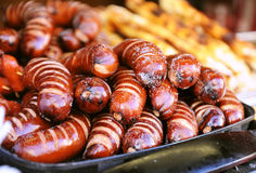 Fried sausages on a platter. Grilled sausages grilled at the fair. Holiday treats stock images