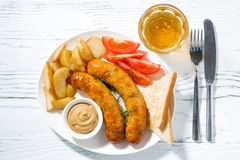 fried sausages with potatoes, mustard and beer, top view Stock Images