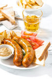 fried sausages with potatoes, mustard and beer, vertical Stock Photo