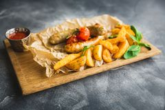 Fried sausages with potatoes and pickled tomato on a wooden plate. Closeup view. Stock Photo