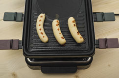Fried sausages on raclette top-table Stock Images
