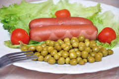 Fried sausages with salad. And peas Stock Photos