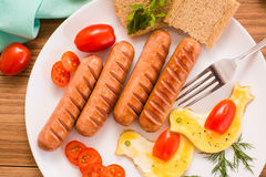 Fried sausages, scrambled eggs, cherry tomatoes and bread. Royalty Free Stock Photography