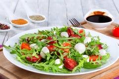 Fried sausages, tomatoes, mini mozzarella, arugula salad. Delicious salad with tomatoes, mini mozzarella, arugula, fried sausages on a white dish on a white Stock Photography