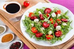 Fried sausages, tomatoes, mini mozzarella, arugula salad. Delicious salad with tomatoes, mini mozzarella, arugula, fried sausages on a white dish on a white Stock Photos