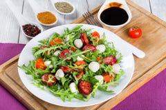Fried sausages, tomatoes, mini mozzarella, arugula salad. Delicious salad with tomatoes, mini mozzarella, arugula, fried sausages on a white dish on a white Stock Photo