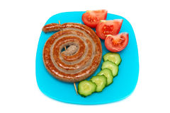Fried sausages with vegetables on a plate. Royalty Free Stock Photo
