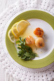 Fried scallops with sauce and lemon on a plate. vertical top vie Royalty Free Stock Photography